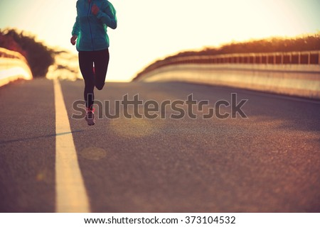 young fitness woman runner running on sunrise road #373104532