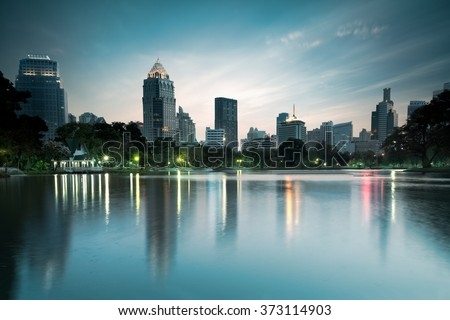 Business district cityscape from a park with twilight time from lumpini park, Bangkok Thailand