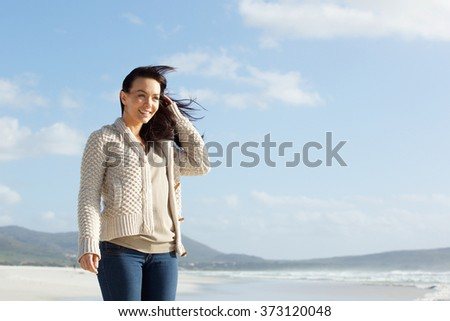 Portrait of relaxed young woman standing on the sea shore #373120048