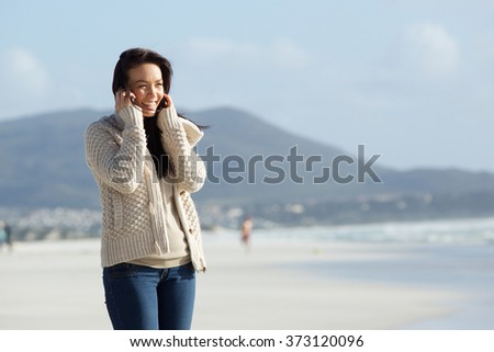 Portrait of a cheerful young lady using mobile phone on the sea shore #373120096