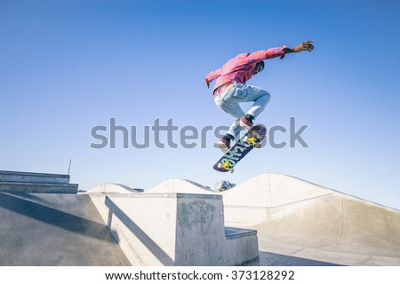 Skateboarder doing a trick in a skate park #373128292