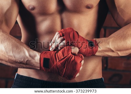 Muscular Fighter With Red Bandages against the background of a brick wall Royalty-Free Stock Photo #373239973