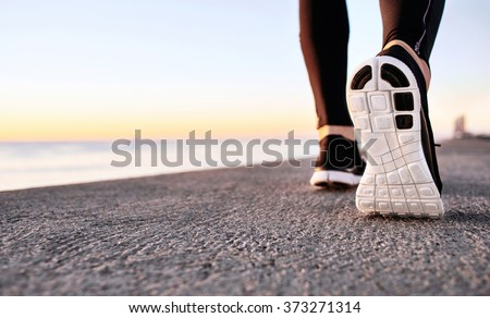 Athlete runner feet running on treadmill closeup on shoe. Jogger fitness shoe in the background and open space around him. Runner jogging training workout exercising power walking outdoors in city. #373271314