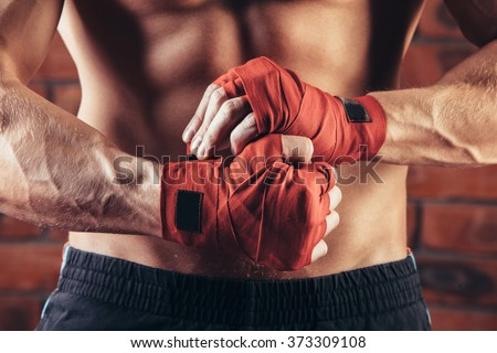 Muscular Fighter kickbox  With Red Bandages against the background of a brick wall Royalty-Free Stock Photo #373309108