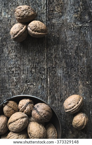 Whole walnuts in a metal bowl on a wooden rustic background, top view. #373329148