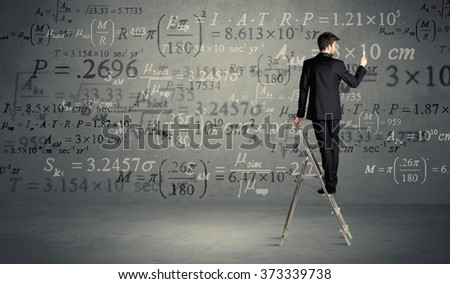 A businessman in elegant suit standing on a small ladder and writing numbers, calculating on grey wall background #373339738