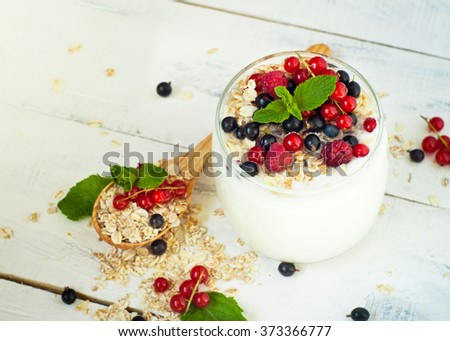 Homemade yogurt with berries and oat flakes in a glass jar #373366777