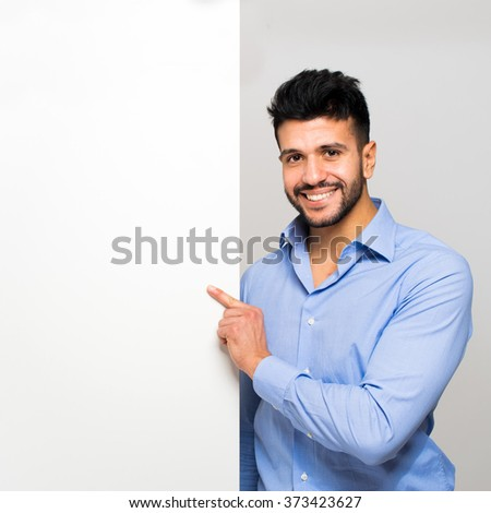 Happy smiling young business man showing blank signboard  #373423627