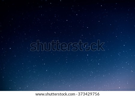 Night sky full of stars and sunrise on the background horizon. Beautiful view from the top of the mountain.