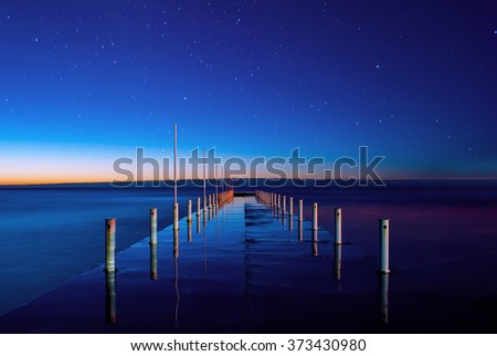 Beautiful night seascape with stars in the sky and pier stretching into the sea. Sunrise on the horizon with orange sky. #373430980