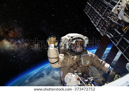Astronaut on space mission with earth on the background. Elements of this image furnished by NASA. #373472752