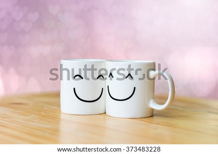 Two happy cups on wood table with Valentine's day hearts bokeh background #373483228
