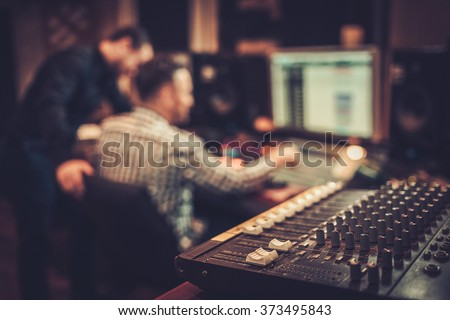 Sound engineer and producer working together at mixing panel in the boutique recording studio. Royalty-Free Stock Photo #373495843