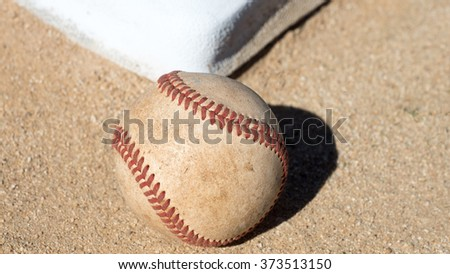 A baseball on the field with a base in the background #373513150
