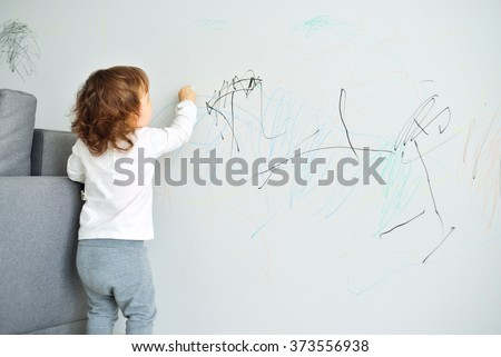 Curly cute little baby girl drawing with crayon color on the wall. Works of child Royalty-Free Stock Photo #373556938