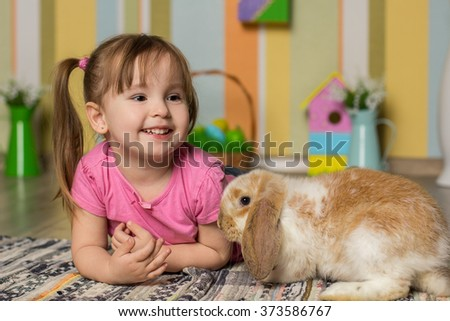 Easter photo. Little cute girl play with rabbit #373586767