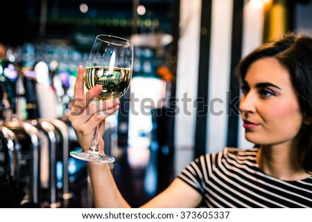 Attractive woman looking at her glass of wine in a bar #373605337