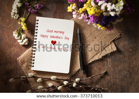 """Good morning Happy valentine's day I will always love you"" is written on opened notebook on wood table with low key scene"