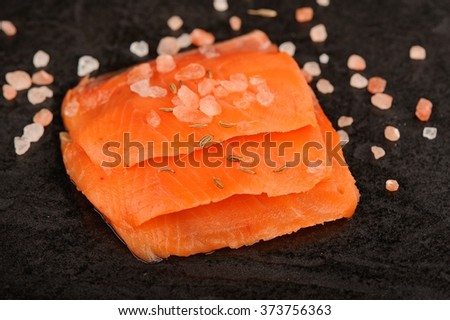 Wild salmon salted with coarse pink himalayan salt on black background #373756363