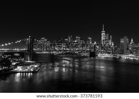black and white picture of the skyline of downtown Manhattan with Brooklyn Bridge and East River in New York City at night