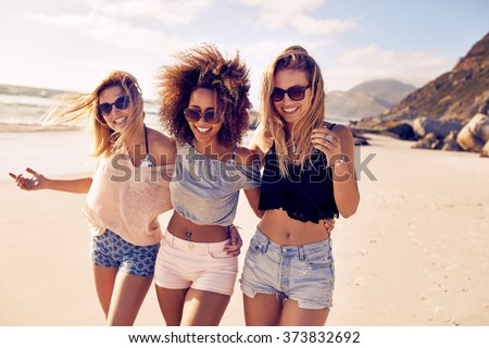 Portrait of three young female friends walking on the sea shore looking at camera laughing. Multiracial young women strolling along a beach. Royalty-Free Stock Photo #373832692