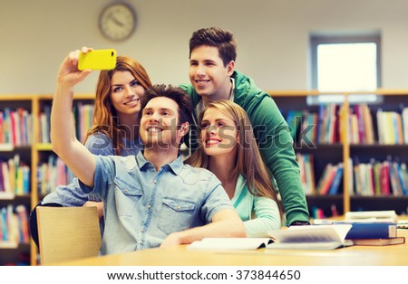 people, technology, education and school concept - happy students or friends with smartphone taking selfie in library