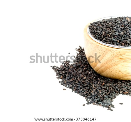 Black sesame seeds in a wooden bowl on a white background. #373846147