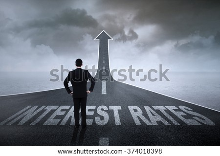 Image of successful entrepreneur standing on the road turning into upward arrow with Interest Rates words on it #374018398