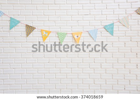 White brick wall decorated by colorful cartoon flag for children