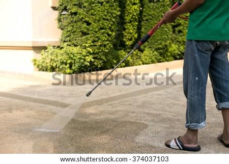 Worker cleaning outdoor floor with high pressure water jet #374037103