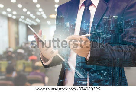 Double exposure of Businessman using the tablet on the Abstract blurred photo of conference hall or seminar room with attendee background #374060395