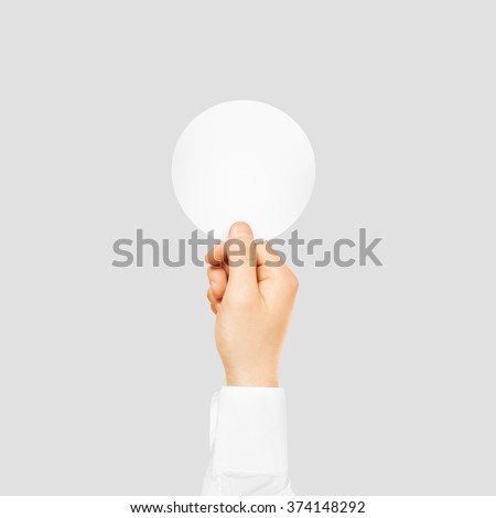 Hand holding round blank white sticker mock up isolated on gray. Sticker mockup holder. Empty paper clue remnder hold in hands. Arm sticking round sticker. #374148292