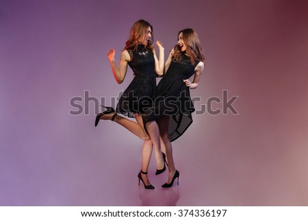 Full length portrait of a cheerful two women in night black dress dancing over purple background  #374336197