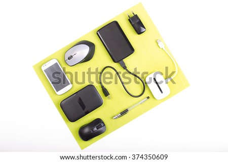 Top view of gadgets on green pad on white desk  #374350609