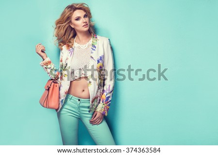Beautiful woman wearing nice clothes, handbag posing on turquoise background. Fashion spring photo #374363584