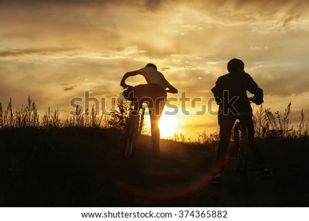 summer landscape silhouette of a boy on a bicycle, with rolling hills on the background of golden sunset  #374365882