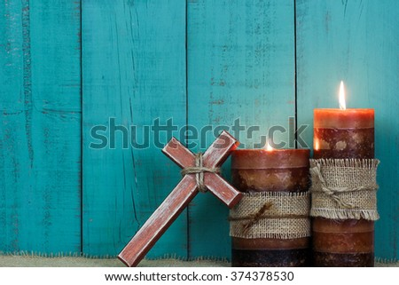 Textured candles burning and rugged wood cross with rope by antique rustic teal blue wooden background; Easter, Christmas, Memorial Day and religious background with copy space
