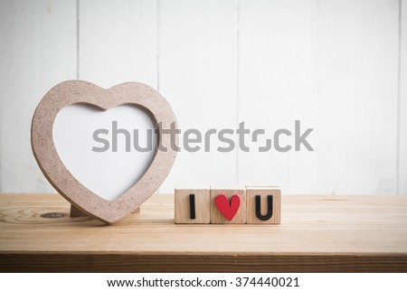 """Heart shaped photo frame with """"i love u"""" in cube on wood table"""