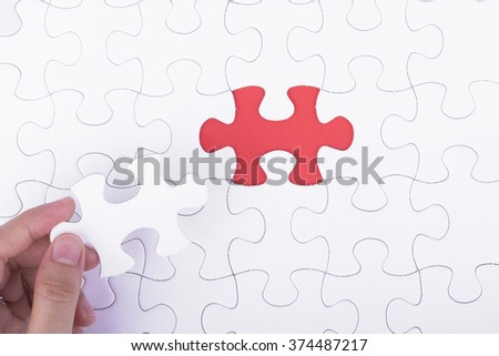 Hand embed missing a piece of puzzle into place, red space concept #374487217