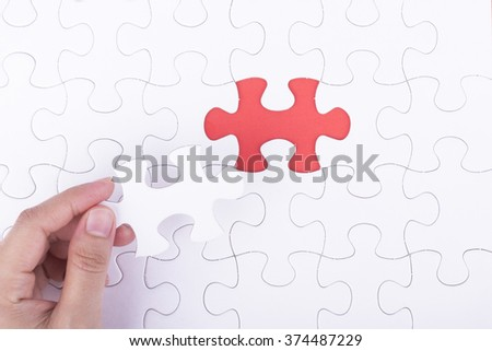 Hand embed missing a piece of puzzle into place, red space concept #374487229