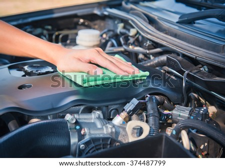 Wipe cleaning the car engine with green microfiber cloth  #374487799