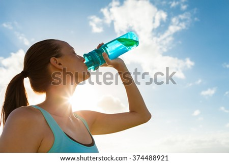 Young female drinking a bottle of water.  Royalty-Free Stock Photo #374488921