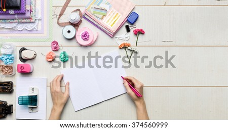 Top view of table with elements for scrapbooking, tools for decoration and handmade albums and hands of master. Royalty-Free Stock Photo #374560999