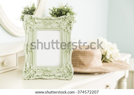 High key photo of Vintage frame on table with hat in front of the mirror, bedroom scene