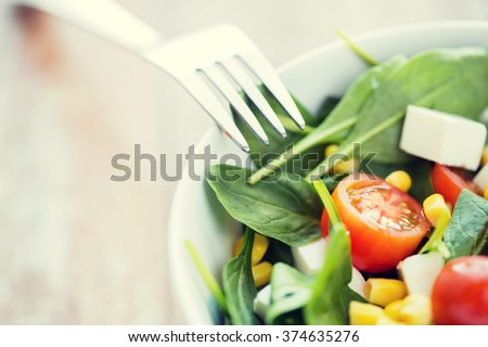 healthy eating, dieting, vegetarian kitchen and cooking concept - close up of vegetable salad bowl and fork at home #374635276