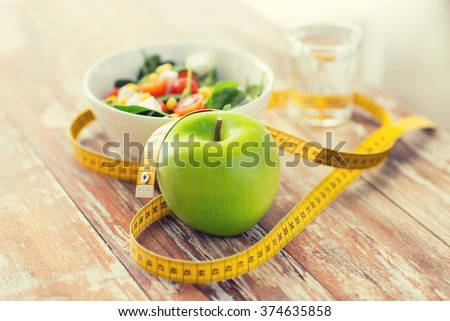 healthy eating, dieting, slimming and weigh loss concept - close up of green apple, measuring tape and salad #374635858