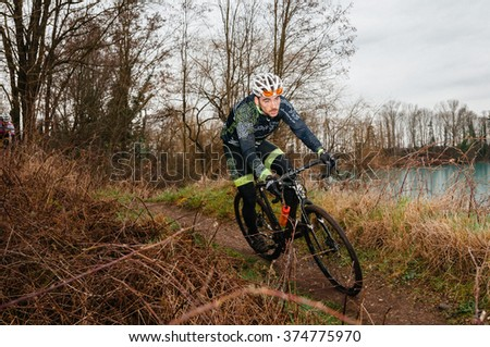 RIMSINGEN, GERMANY - February 7: Cyclocross competitors race against each other during a racing simulation in Rimsingen, Germany on 02/07/16.  #374775970