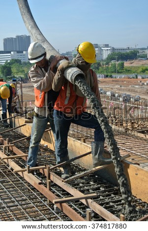 SELANGOR, MALAYSIA - MAY 2014: Construction workers are doing the concrete work using hose from the concrete pump crane on May 15, 2014 at Sepang, Malaysia.  #374817880