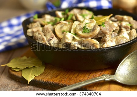 Beef stroganoff with mushrooms in a skillet pan on rustic background. #374840704
