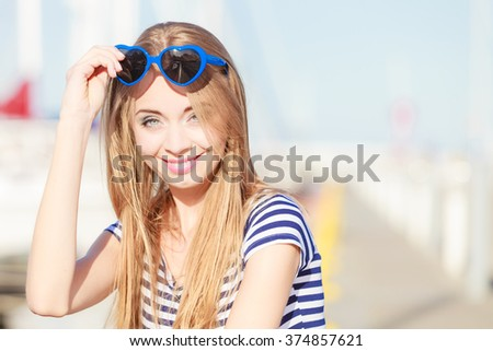Travel tourism and people concept. Fashion blonde girl with blue heart shaped sunglasses in marina against yachts in port #374857621